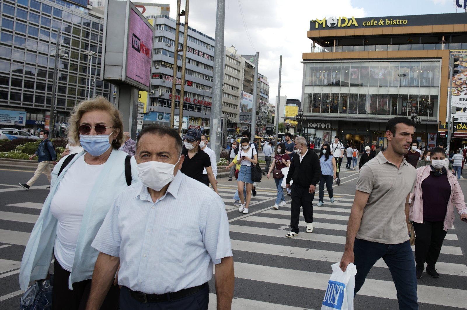 People wearing face masks to protect against the spread of coronavirus, walk in the main Kızılay Square, in Ankara, Turkey, Tuesday, June 16, 2020. (AP Photo)