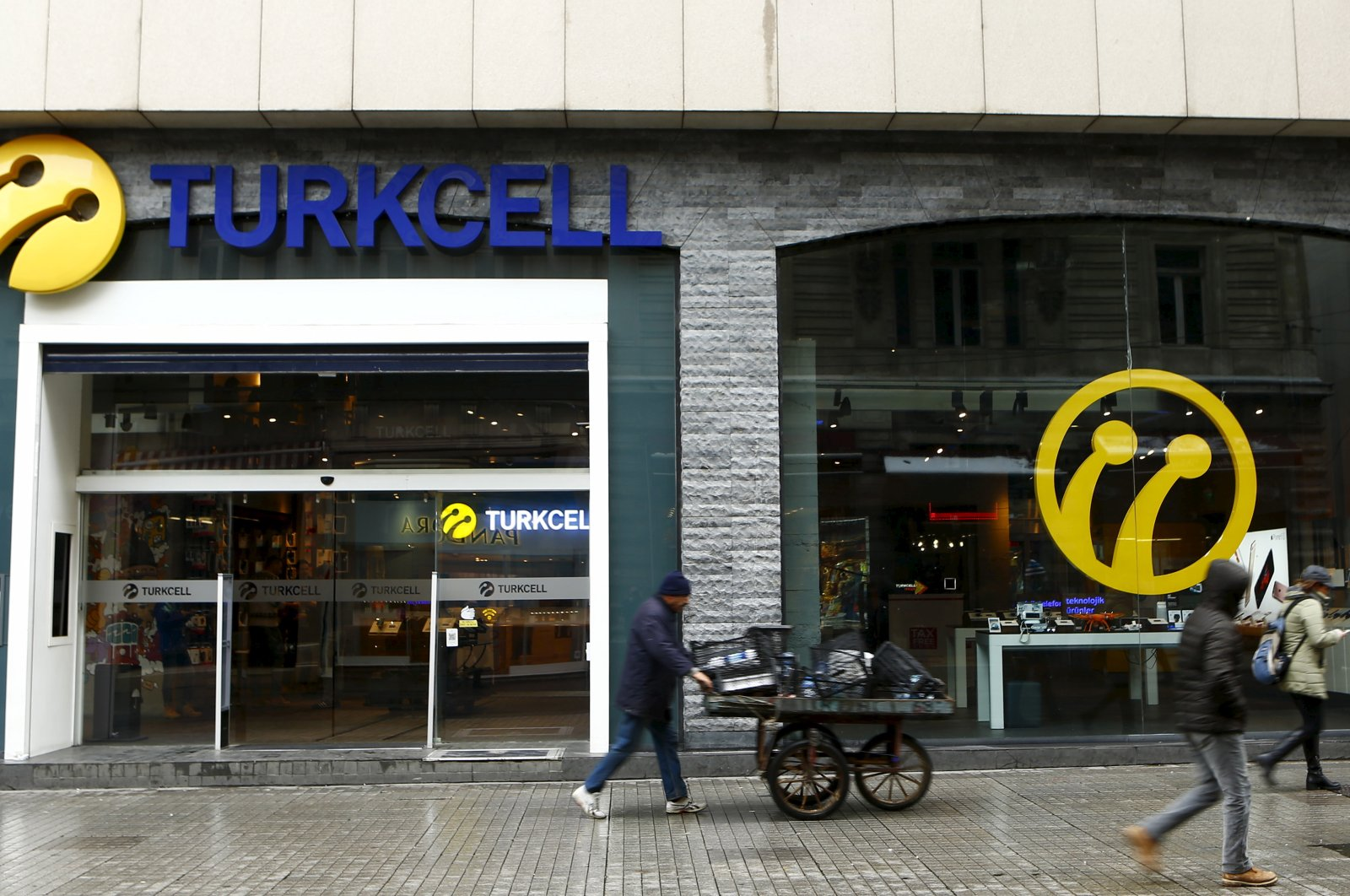 Pedestrians walk past by the main Turkcell shop in central Istanbul, Turkey, Jan. 18, 2016.