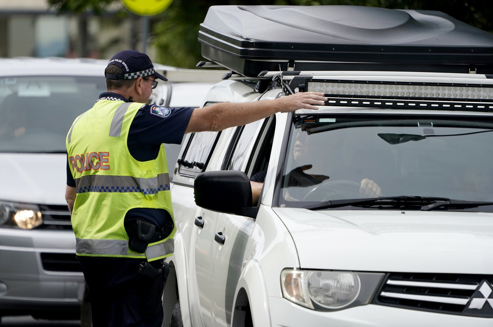 A Queensland police officer gestures for a motorist to pull over at a checkpoint at Coolangatta on the Queensland-New South Wales border, May 22, 2020. (Reuters Photo)
