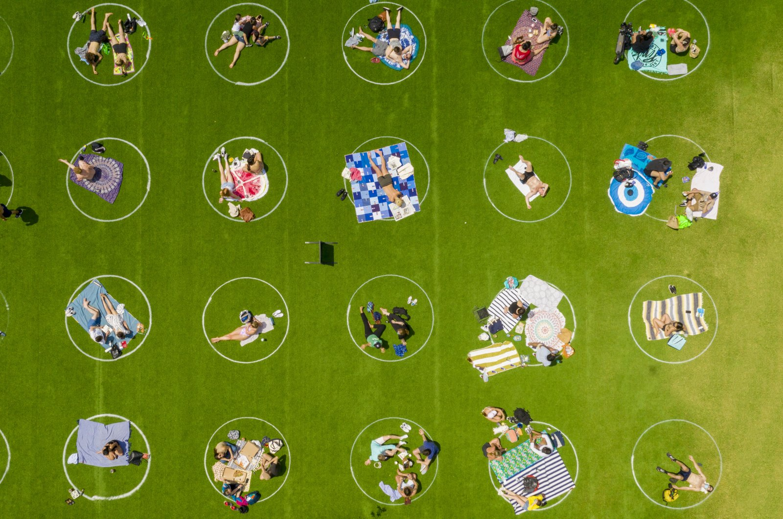 Domino Park in Brooklyn paints circles on the grass to assist visitors in maintaining social distancing, New York City, New York, U.S., May 20, 2020.  (Reuters Photo)