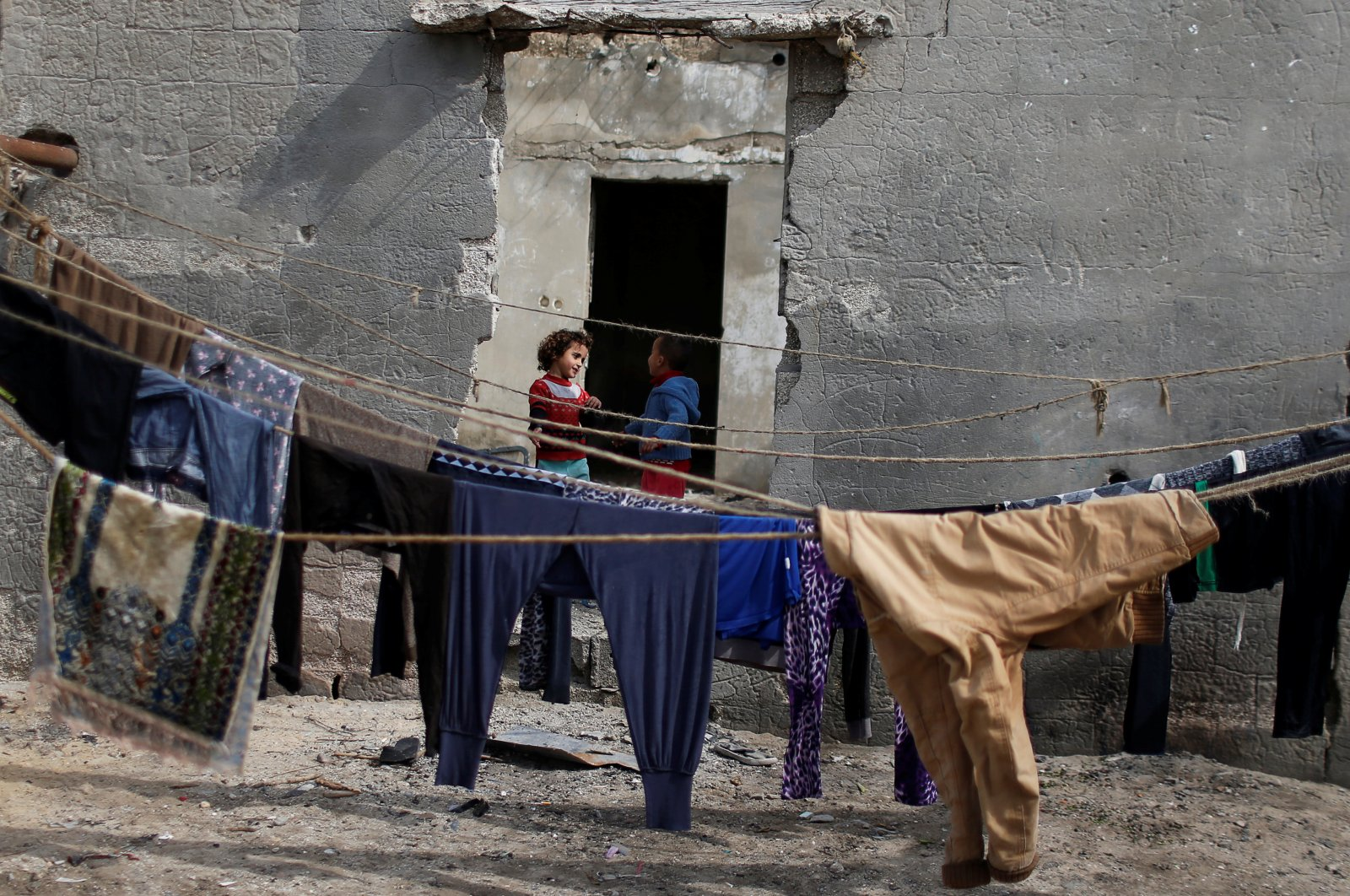 Palestinian children stand outside their house as laundry hangs on ropes at Shati refugee camp in Gaza city, Palestine, Feb. 19, 2020. (Reuters Photo)