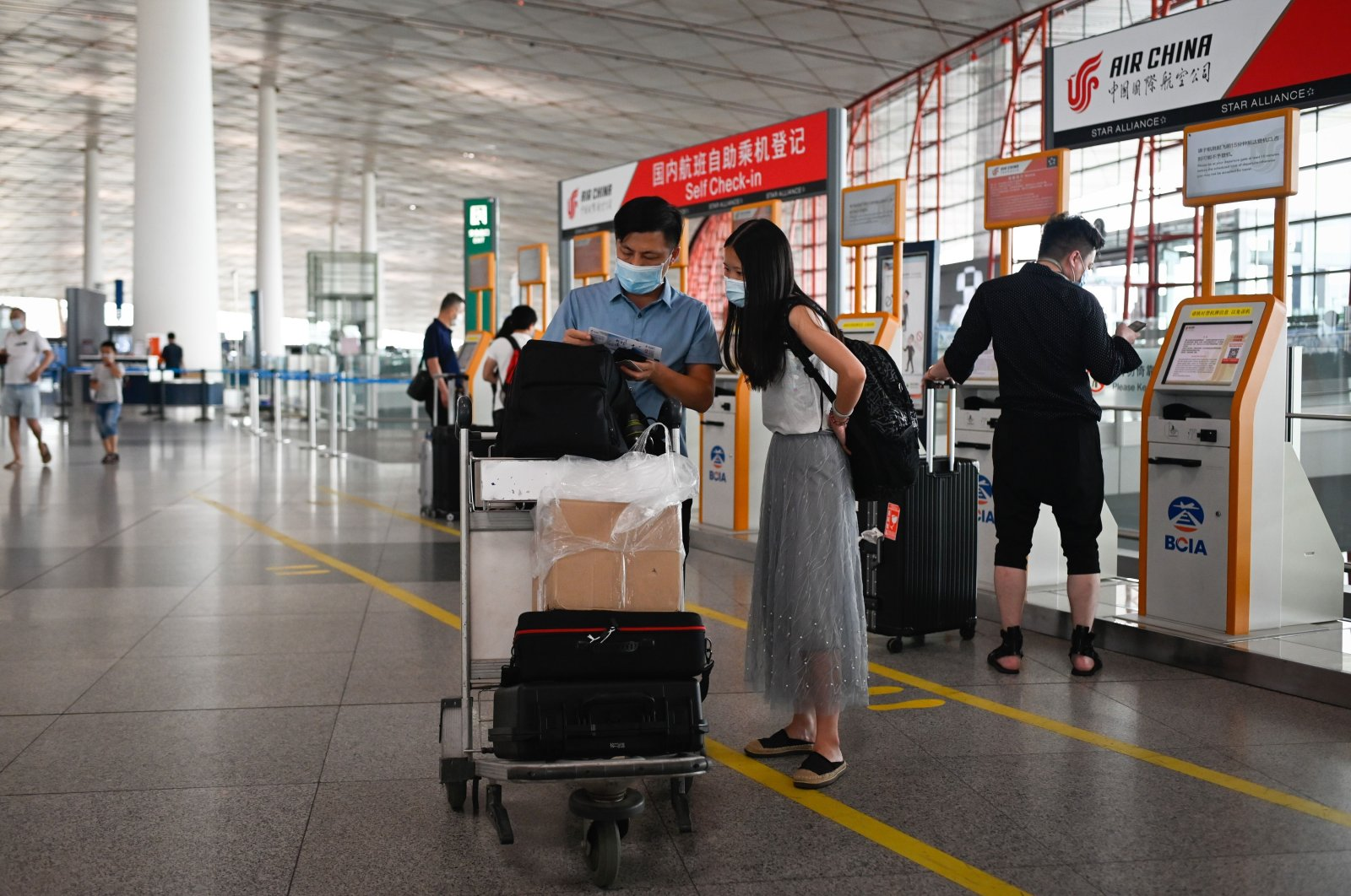 Travelers wearing face masks inspect their tickets after conducting self-check-in procedures at the Beijing International Airport, Beijing, China, June 17, 2020. (AFP Photo)