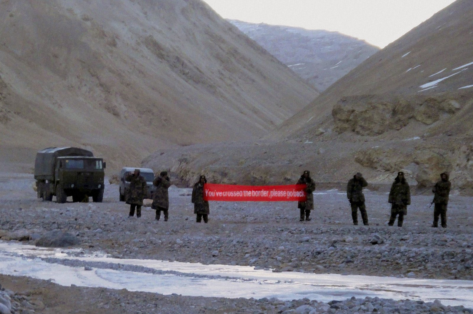 """In this file photo, Chinese troops hold a banner that reads: """"You've crossed the border, please go back"""" in Ladakh, India, May 5, 2013. (AP Photo)"""
