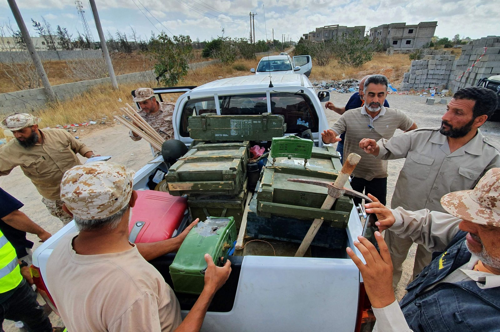 Libyan deminers stand around a pickup carrying boxes of dismantled mines and recovered remnants of ammunition in the Salah al-Din area, south of the Libyan capital Tripoli, June 15, 2020. (AFP Photo)