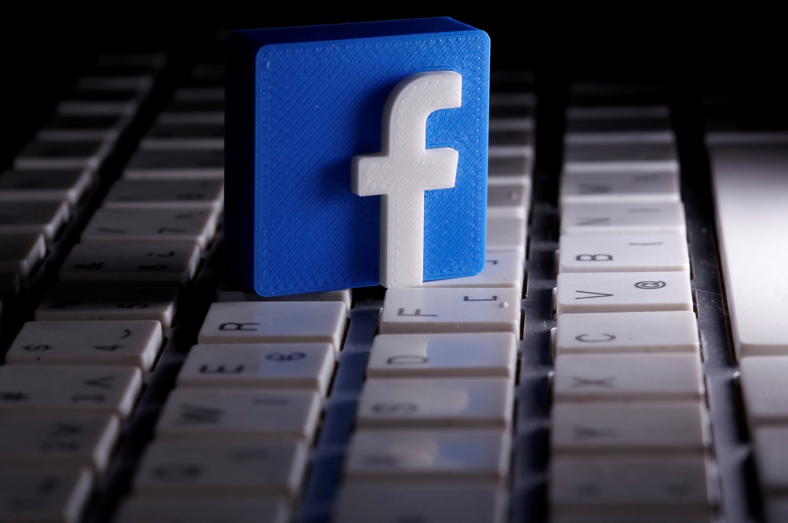 A 3D-printed Facebook logo is seen placed on a keyboard in this illustration, March 25, 2020. (Reuters Photo)