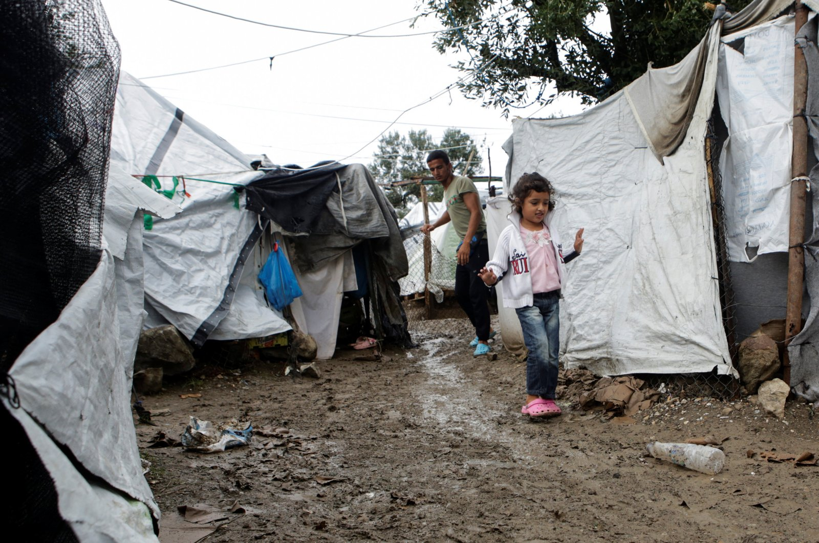 A girl walks next to tents at a makeshift camp for refugees and migrants next to the Moria camp, following rainfall on the island of Lesbos, Greece, Oct. 8, 2019. (Reuters Photo)