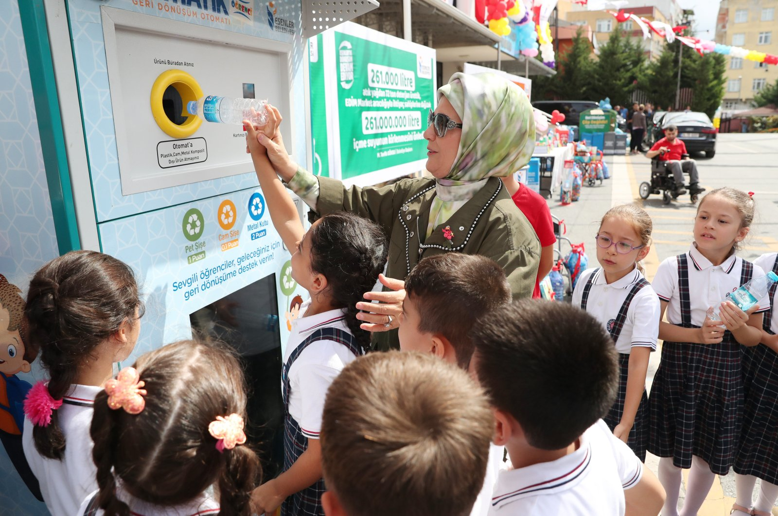 First lady Emine Erdoğan dumps a plastic bottle into a recycling bin at an event to promote the Zero Waste project among students at a school in Istanbul, Turkey, in this undated photo. (AA Photo)