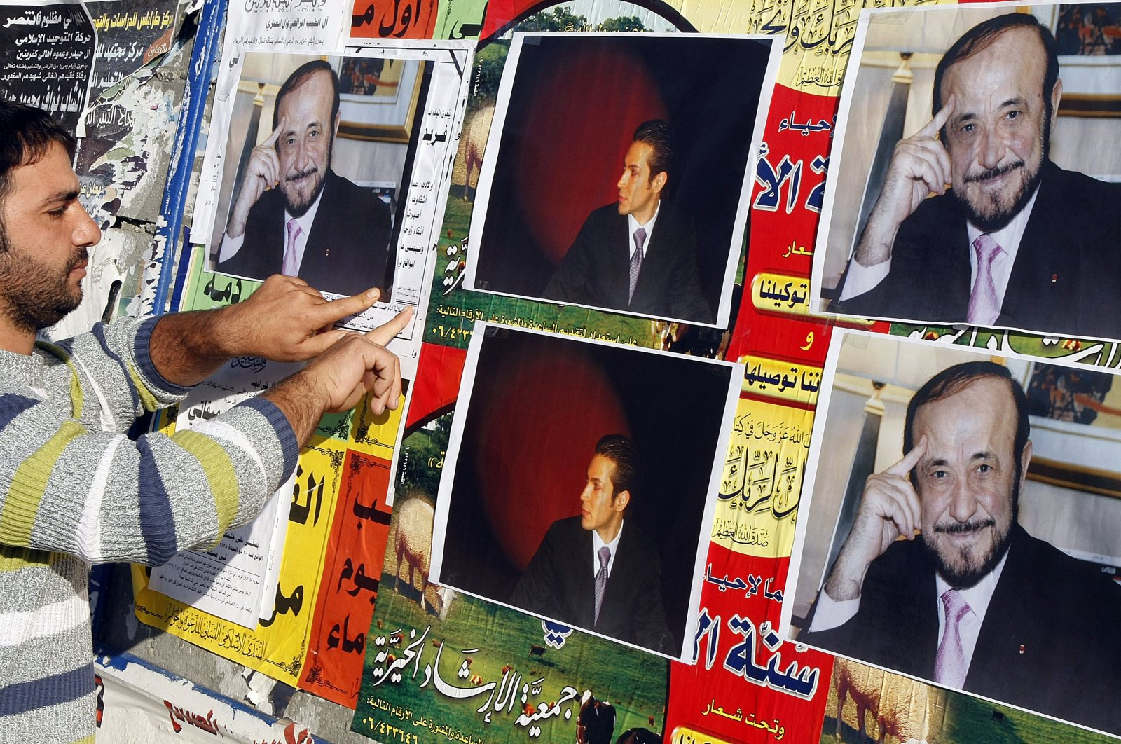 A man pastes pictures of Rifaat Assad (R), the younger brother of late Syrian President Hafez Assad and uncle of Bashar Assad, and Rifaat Assad's son Ribal on a wall in the northern city of Tripoli, Lebanon, Dec. 6, 2007. (AFP Photo)