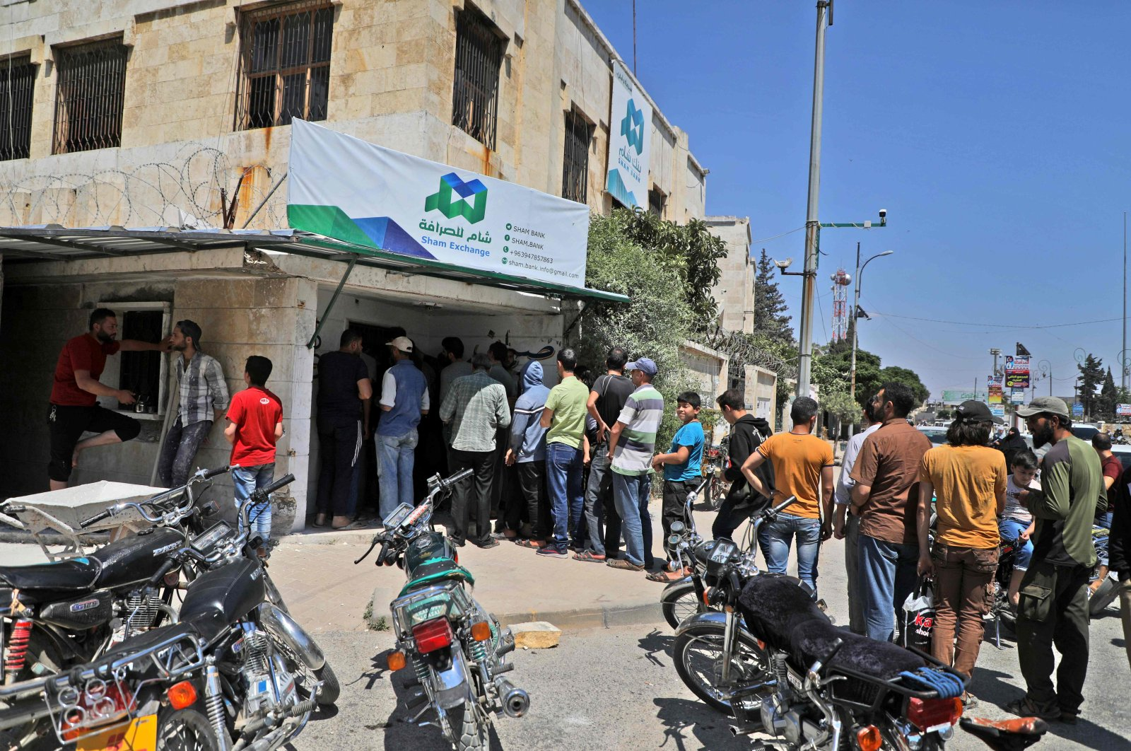 Syrians queue outside a currency exchange shop in Syria's northwestern city of Idlib, June 15, 2020. (AFP Photo)