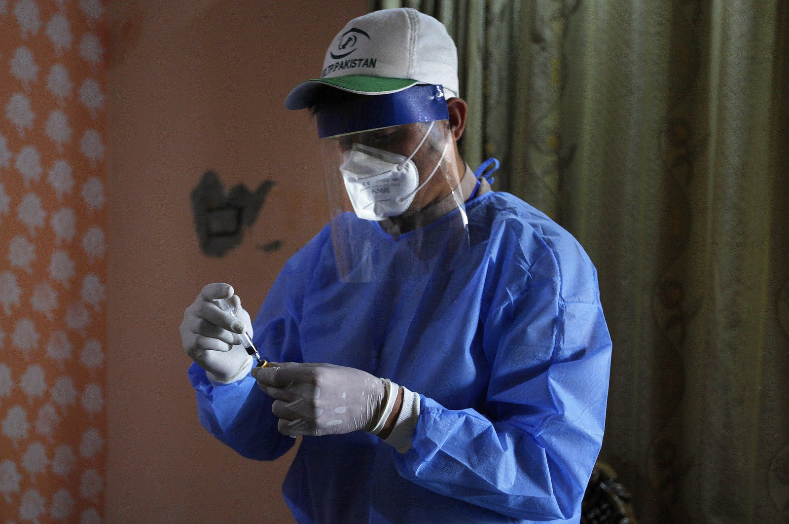 A health worker preserves a blood sample of a boy during door-to-door testing and screening facility for the coronavirus, June 10, 2020. (AP Photo)