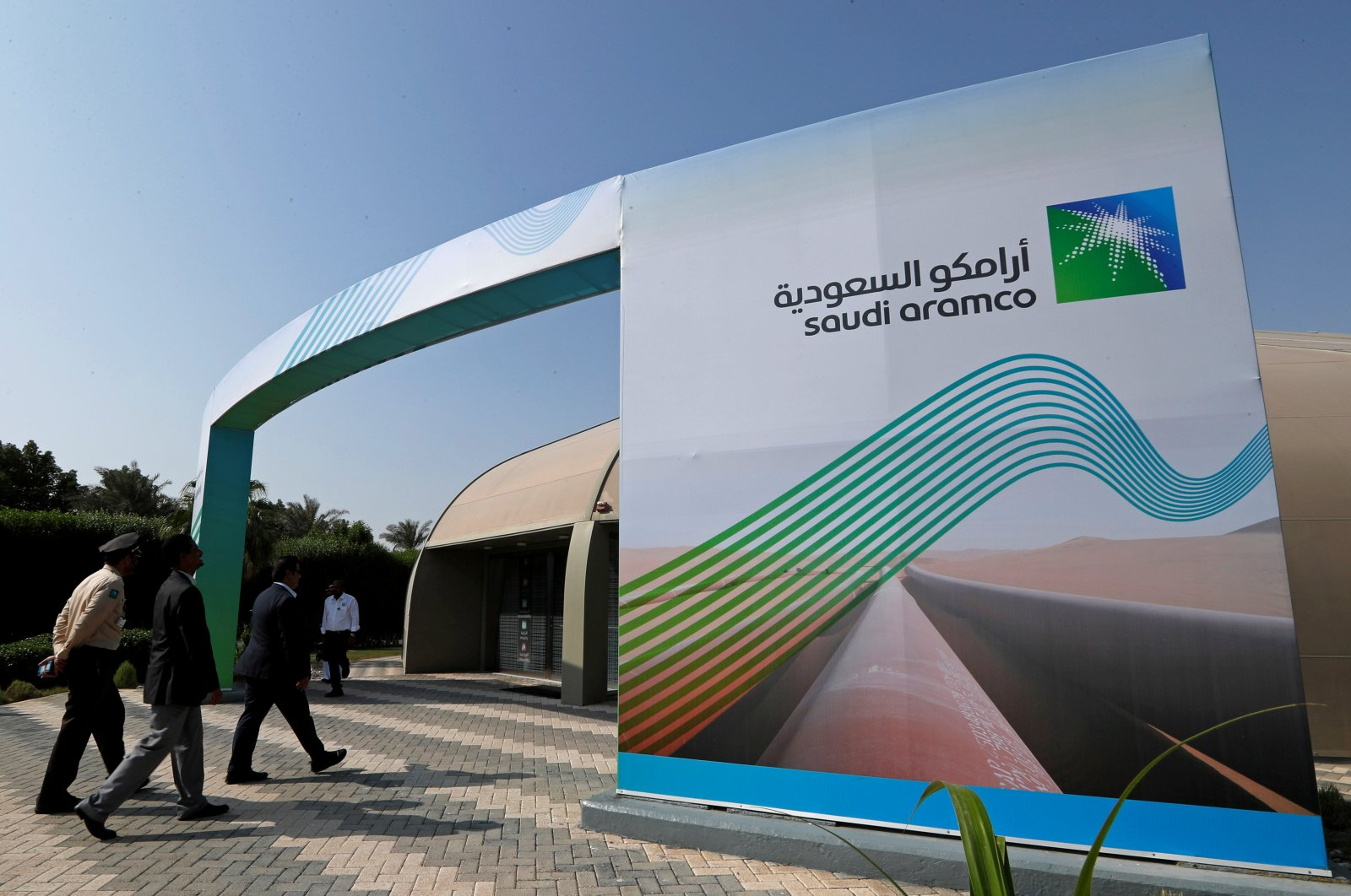 The logo of Aramco is seen as security personnel walk before the start of a press conference by Aramco at the Plaza Conference Center in Dhahran, Saudi Arabia, Nov. 3, 2019. (Reuters Photo)