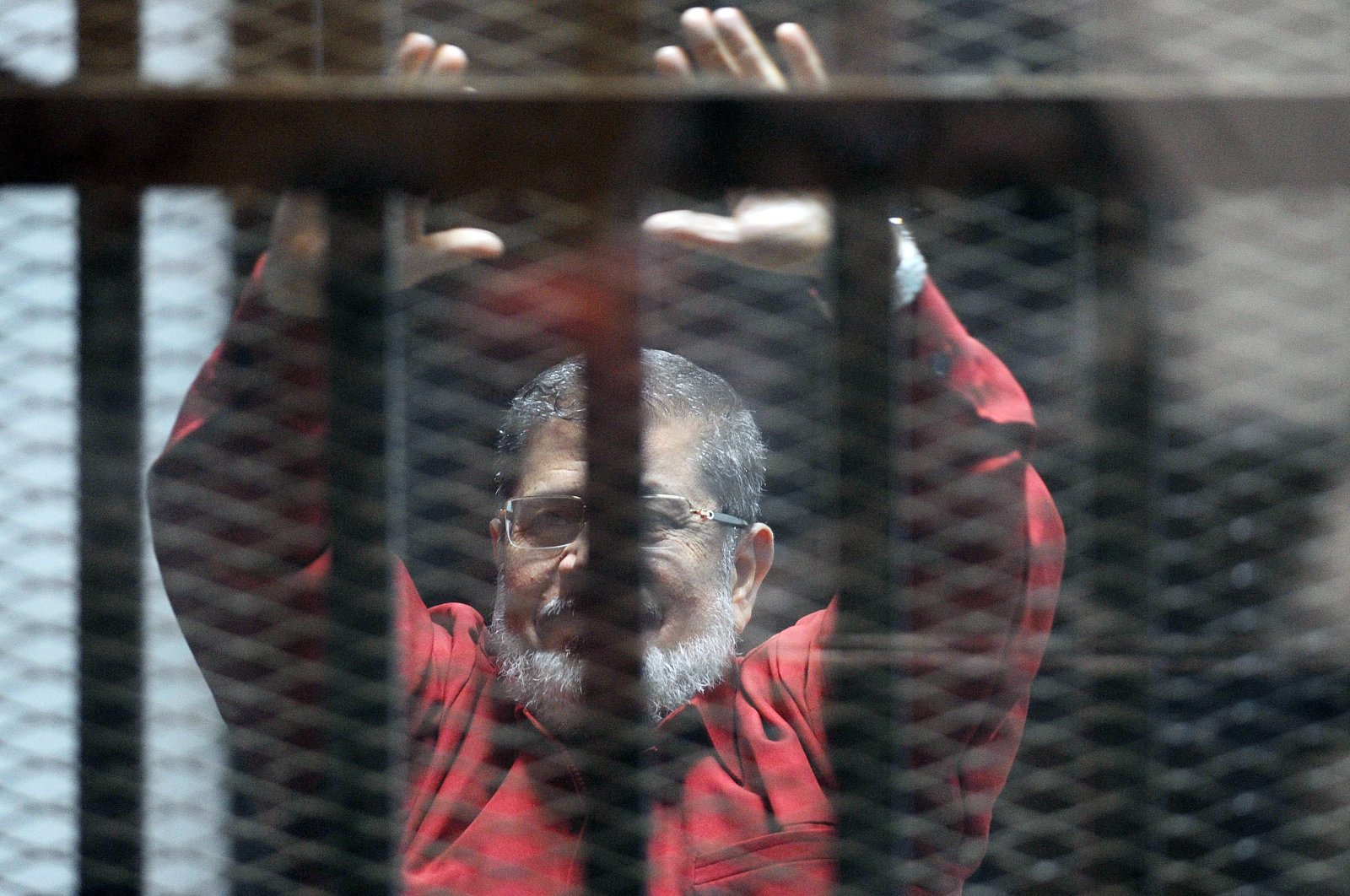 Egypt's first democratically elected President Mohammed Morsi, wearing a red uniform, stands behind bars during his trial in Cairo, June 21, 2015. (AFP Photo)