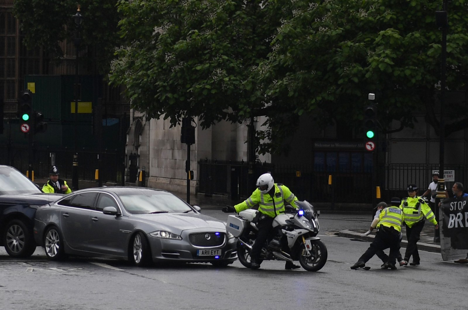 A protester from a demonstration is stopped and detained by police officers as he ran towards the car of Britain's Prime Minister Boris Johnson (C) as it was leaving with a police escort from the Houses of Parliament, London, June 17, 2020. (AFP Photo)