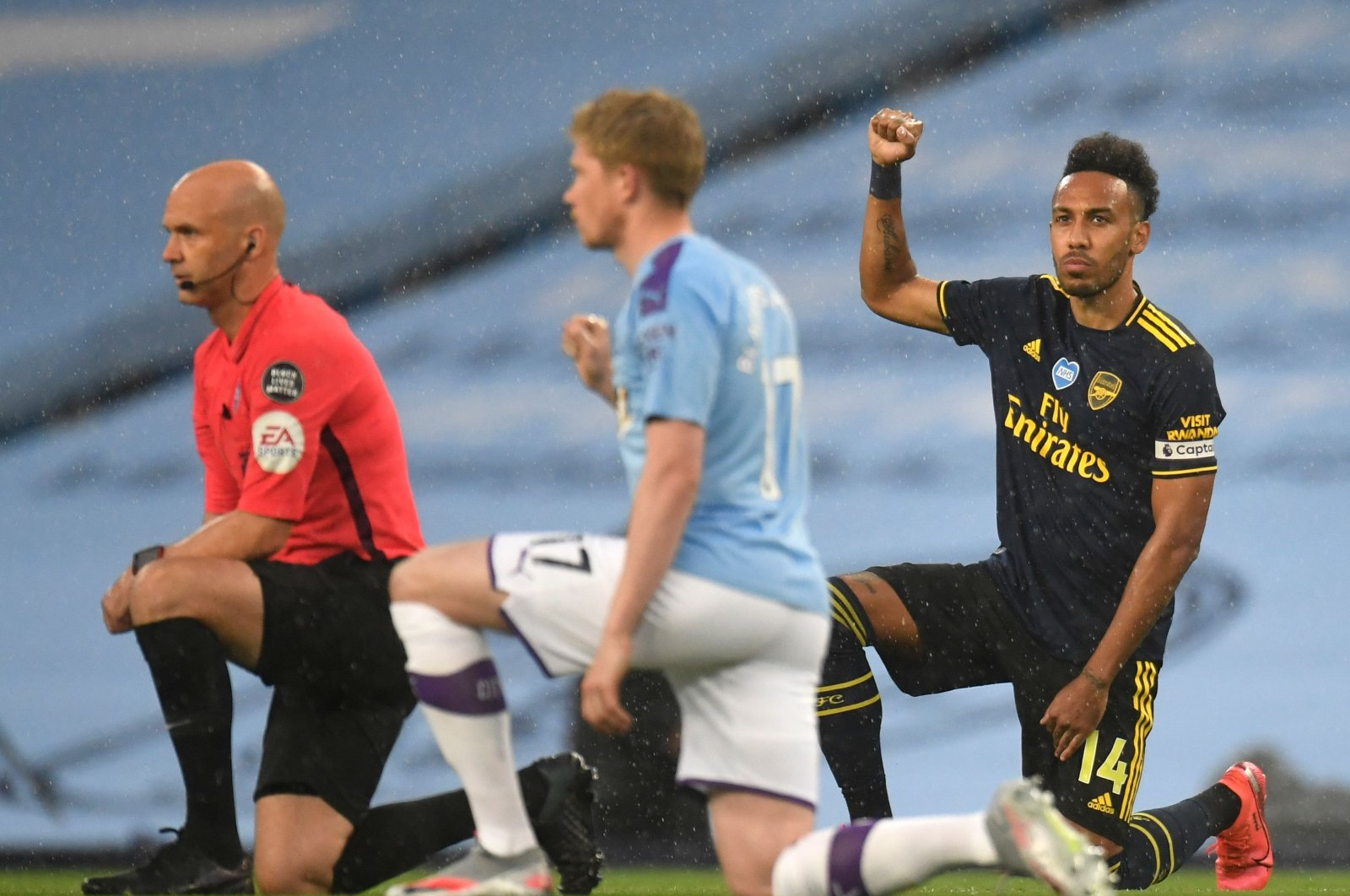 Arsenal's Gabonese striker Pierre-Emerick Aubameyang (R) takes a knee alongside Manchester City's Belgian midfielder Kevin De Bruyne (C) and Referee Anthony Taylor (L) ahead of the English Premier League football match between Manchester City and Arsenal at the Etihad Stadium in Manchester, northwest England, June 17, 2020. (AFP Photo)