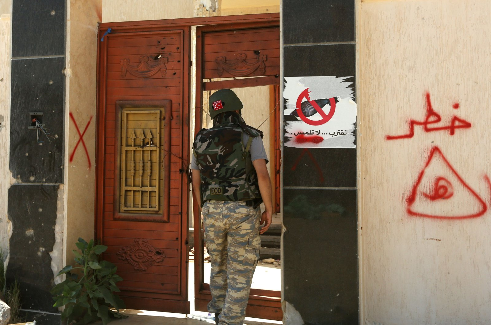 A Turkish deminer stands at the entrance of a house marked with a warning about the presence of mines in the Salah al-Din area, south of the Libyan capital Tripoli, on June 15, 2020. (AFP Photo)