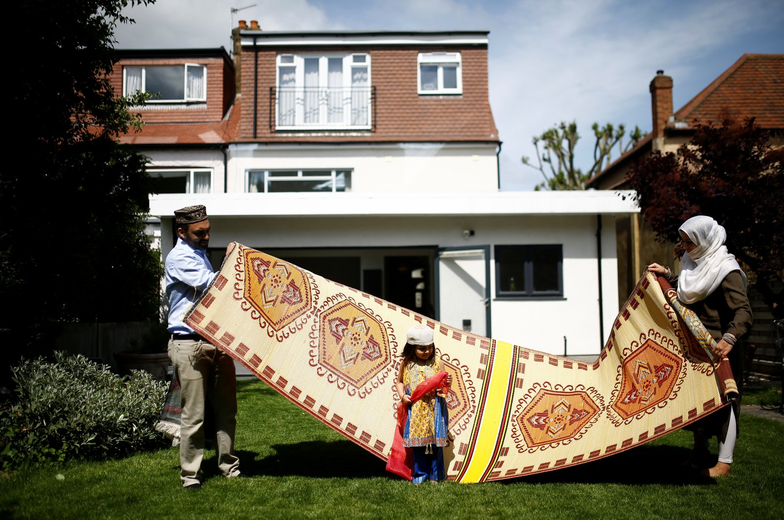 A Muslim family sets up prayer mats in their home garden for the Eid al-Fitr prayers to mark the end of the month of Ramadan following the outbreak of the coronavirus in Surbiton, London, U.K., May 24, 2020. (Reuters Photo)