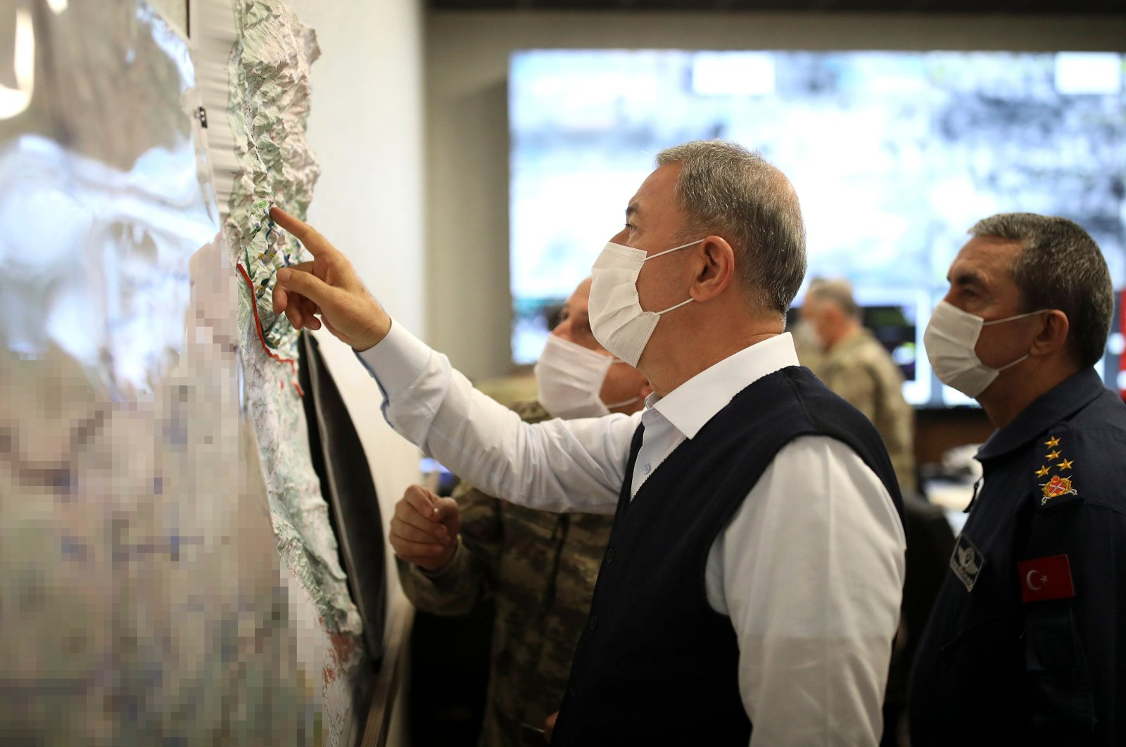 """Defense Minister Hulusi Akar looks at a map with members of the Turkish Armed Forces Command during a meeting at the Army Command Control Center in Ankara during the military operation dubbed """"Claw-Tiger"""" on June 17, 2020. (AFP Photo)"""