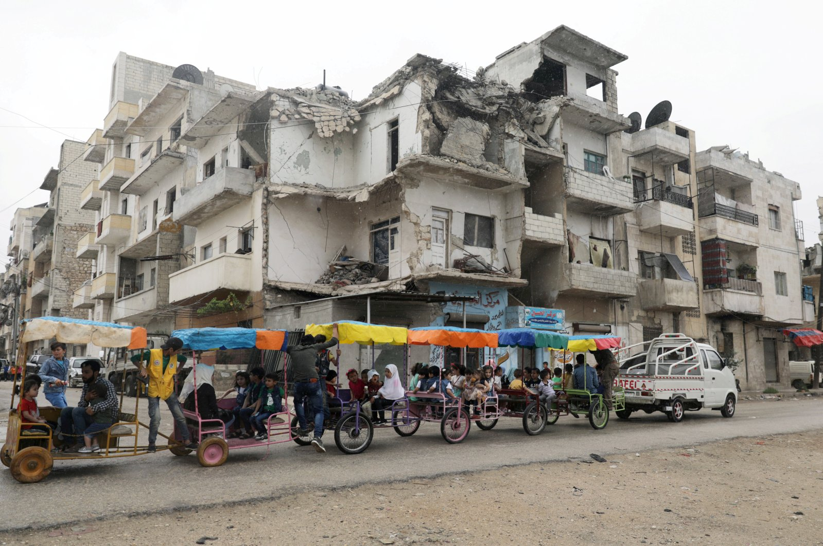 Children ride in carts past a damaged building on the first day of the Muslim holiday of Eid al-Fitr amid the global outbreak of the coronavirus, in the opposition-held Idlib city, northwest Syria, May 24, 2020. (REUTERS Photo)