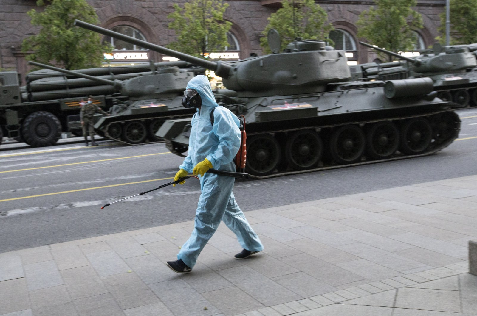 A municipal employee in a protective suit disinfects an area as a measure against the coronavirus outbreak while World War II Soviet-made tanks wait to start a rehearsal for the Victory Day military parade in Moscow, Russia, June 17, 2020. (AP Photo)