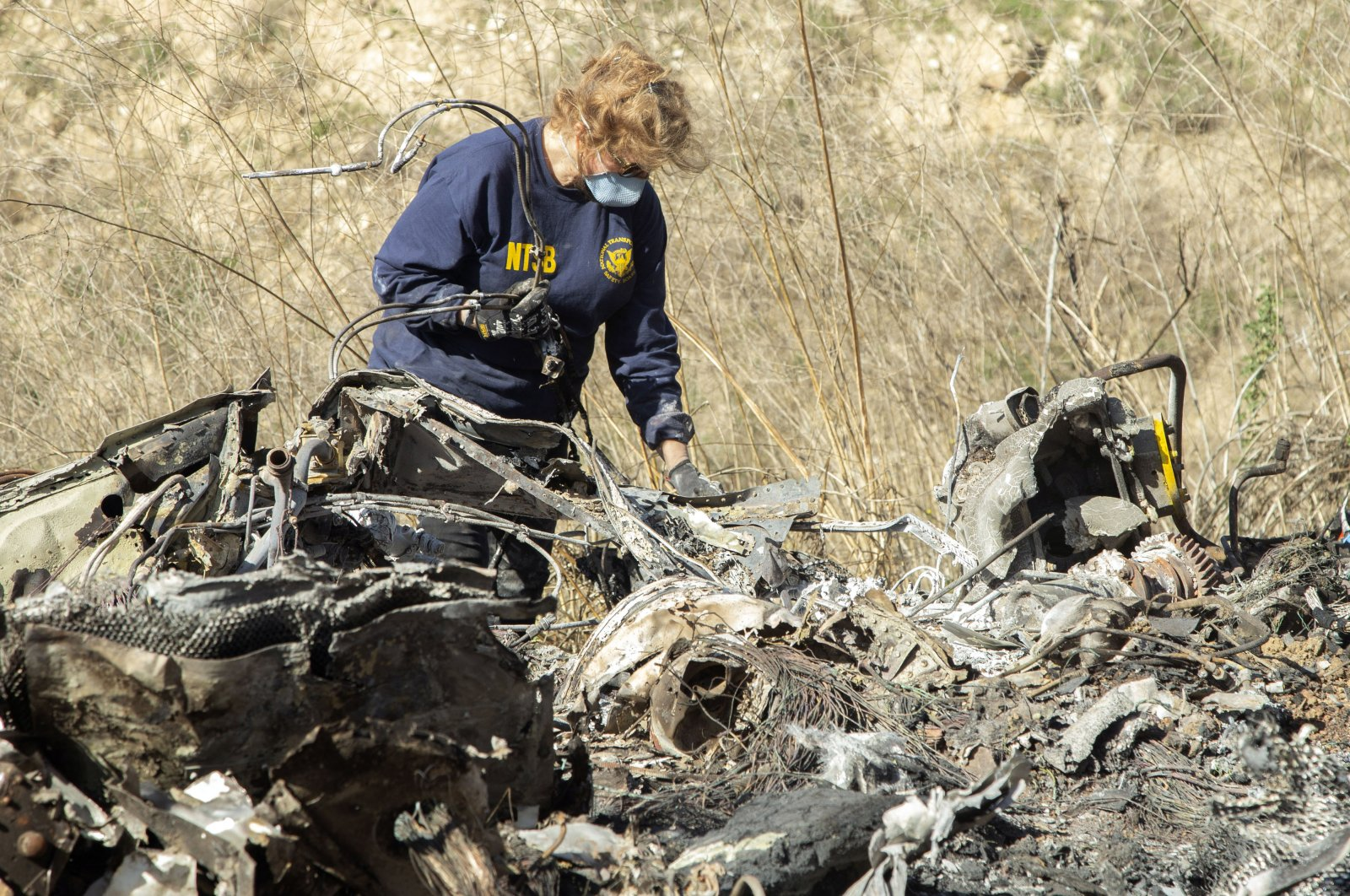 An NTSB investigator examines wreckage as part of the investigation of a helicopter crash that killed former NBA basketball player Kobe Bryant, his 13-year-old daughter, Gianna, and seven others, near Calabasas, California, U.S., Jan. 27, 2020. (AP Photo)