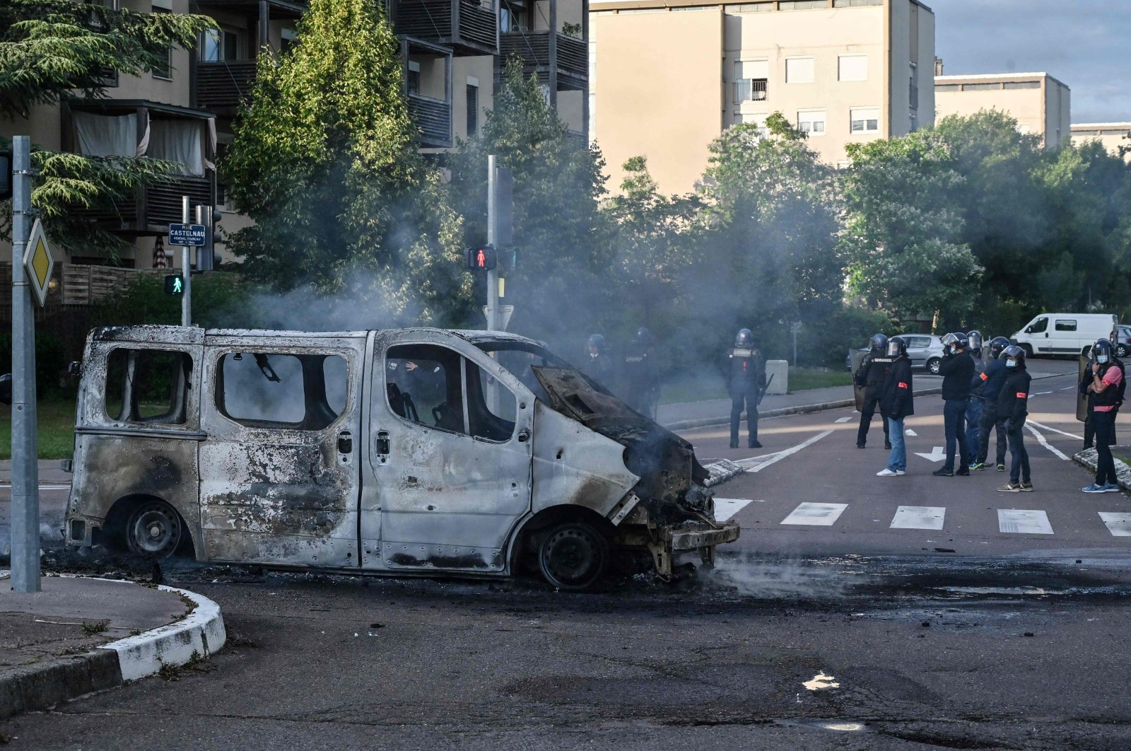 Police and gendarmes stand near a burnt van in the Gresilles area of Dijon, France, June 15, 2020. (AFP Photo)
