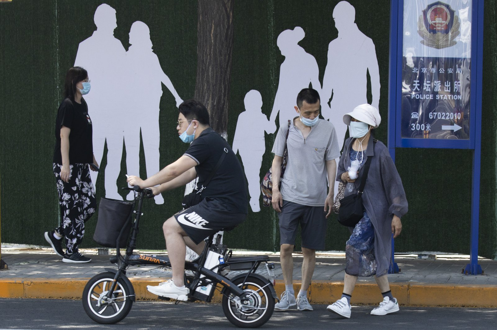 Residents wear masks to curb the spread of the coronavirus on a street of Beijing, June 18, 2020. (AP Photo)