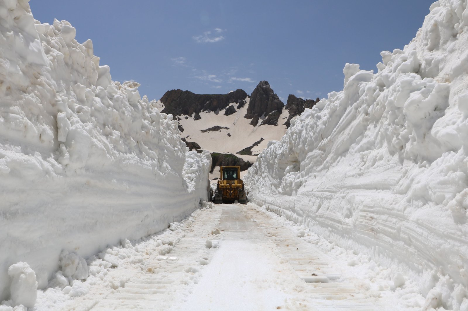A snowplow rolls through columns of snow in Yüksekova district, in Hakkari, Turkey, June 18, 2020. (DHA Photo)