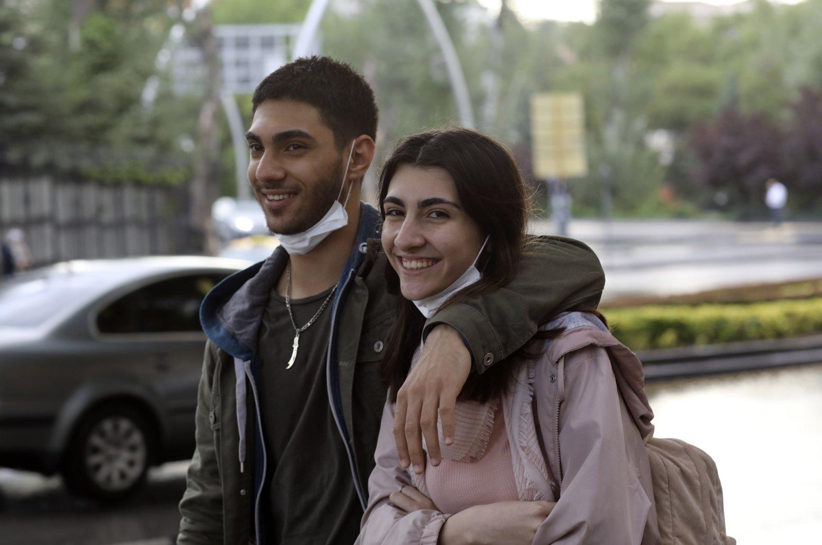 A couple not wearing their masks properly walks in a popular street, in Ankara, Turkey, June 17, 2020. (AP Photo)