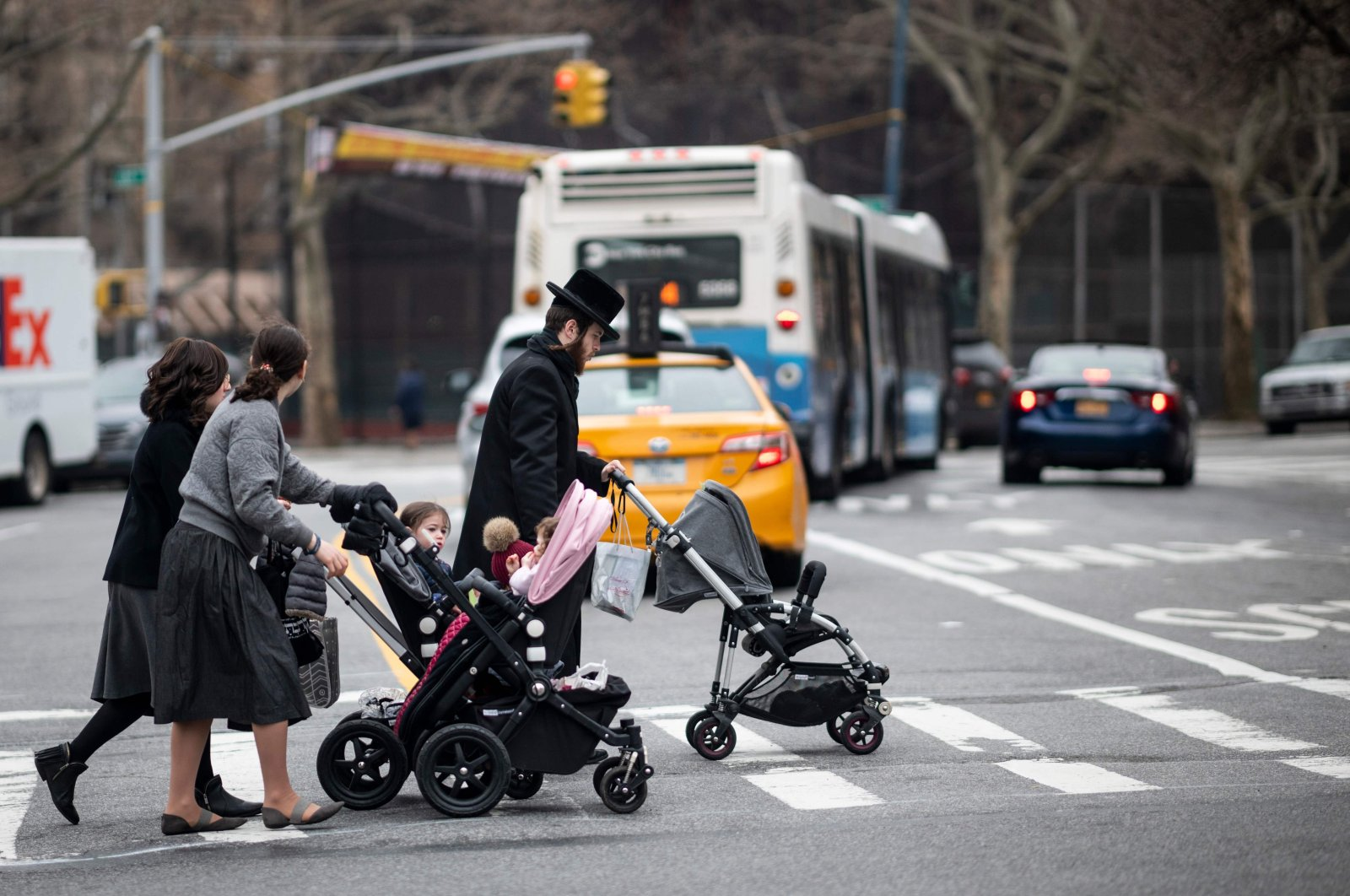 A Jewish man and two woman pushes strollers as they cross a street in a Jewish quarter in Williamsburg Brooklyn, New York City, April 9, 2019. (AFP Photo)