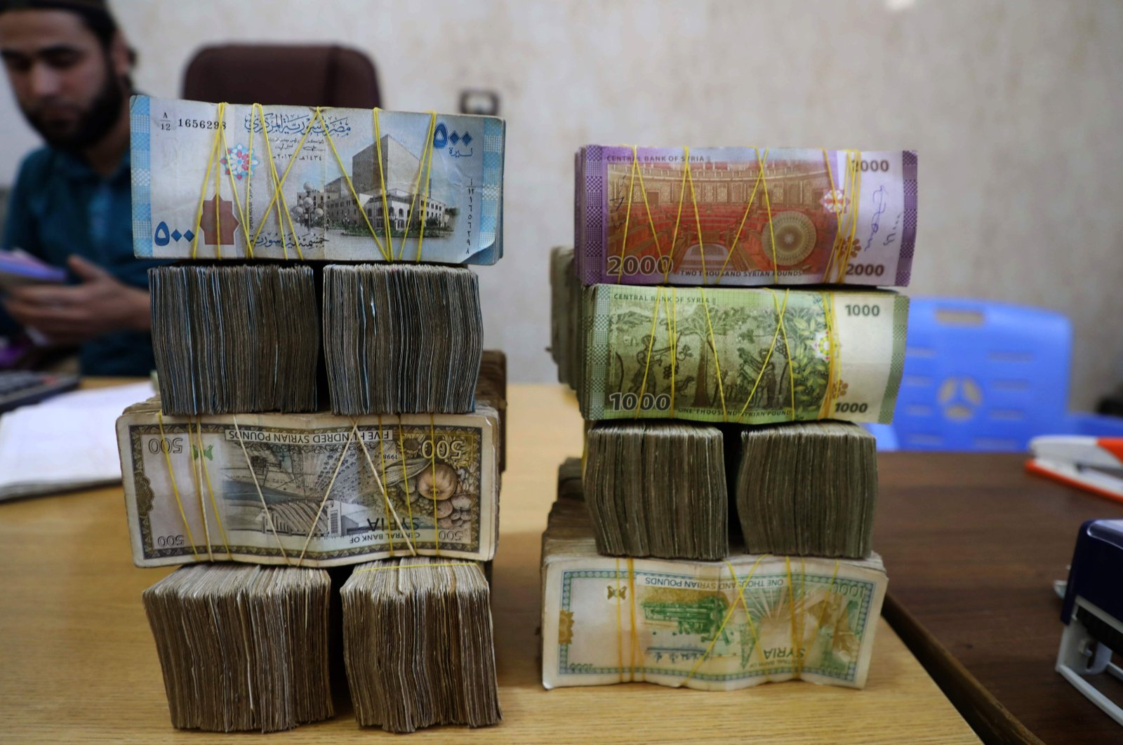 Syrian pounds are pictured at a currency exchange shop in the town of Sarmada in Syria's northwestern Idlib province, June 15, 2020. (AFP)