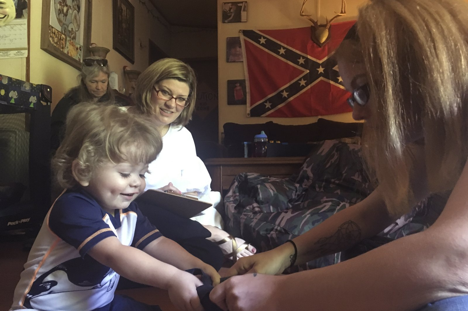 In this May 7, 2018, file photo, Casey Britton, right, works with her younger son, Gavin, on early childhood lesson at their home in Linden, Tenn., as advocates from an anti-poverty group, (AP Photo)