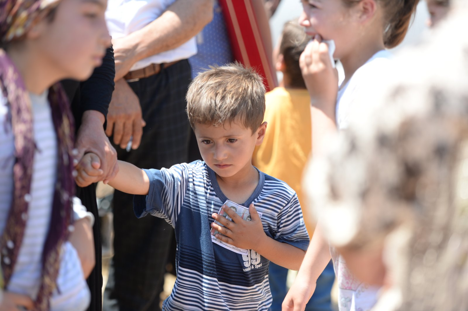 4-years-old child of Hacı Atilla, one of the four victims of the Wednesday's PKK terrorist attack took place in Şırnak, holds the picture of his father during Atilla's funeral, June 18, 2020. (AA)