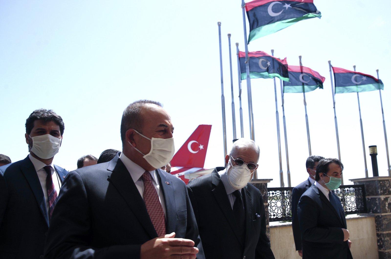 Foreign Minister Mevlüt Çavuşoğlu, left, and Muhammed Tahir Siyala, Foreign Minister of Libya's internationally-recognized government, speak at the airport, in Tripoli, Libya, June 17, 2020. (AP)