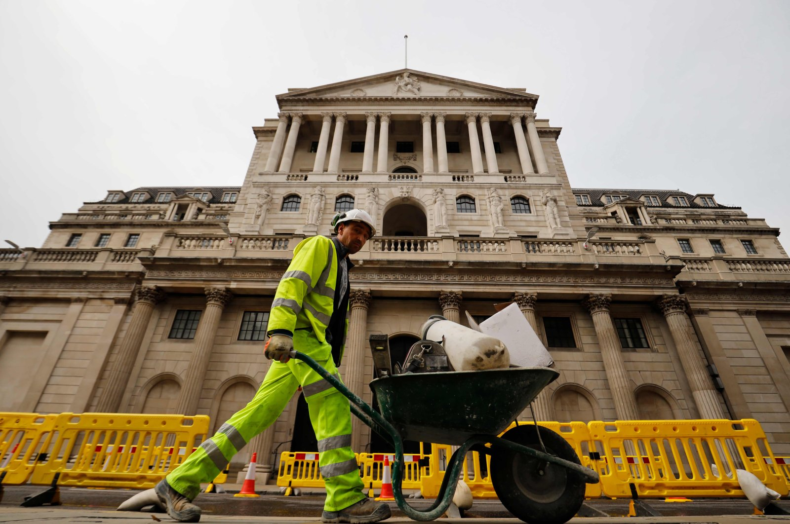 A worker pushes a wheelbarrow of debris outside the Bank of England in London, June 17, 2020. (AFP)