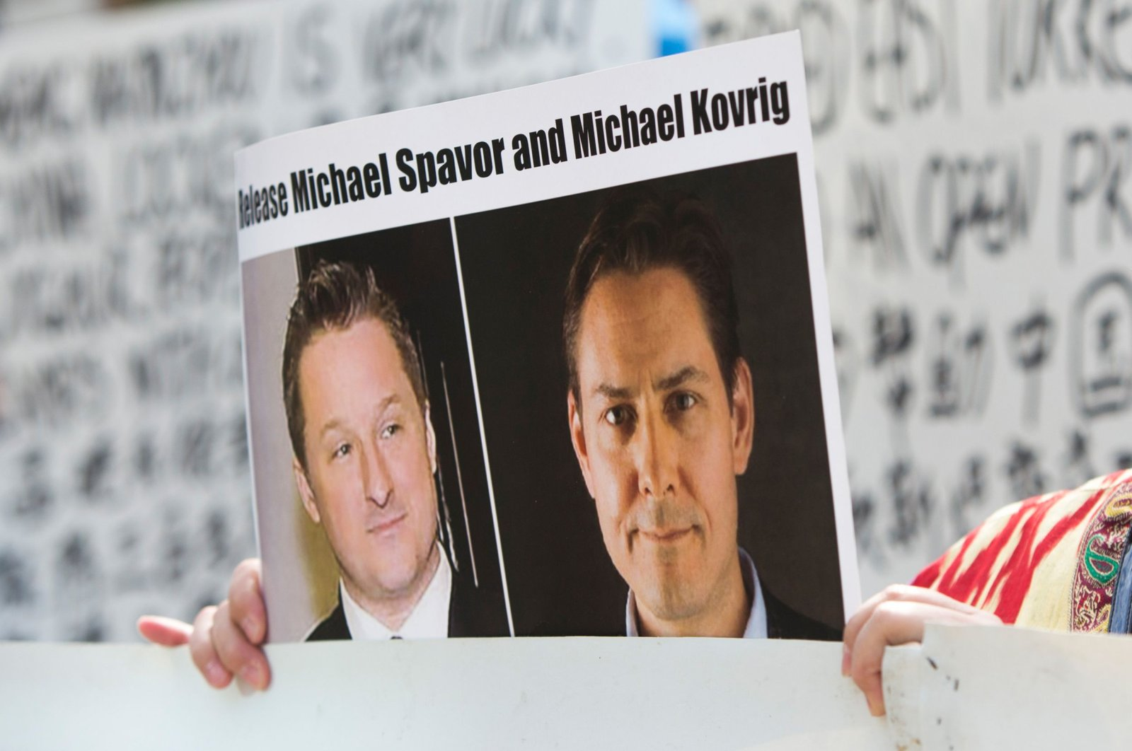 In this May 8, 2019, file photo, a protester holds up a placard depicting detained Canadians Michael Spavor, left, and Michael Kovrig outside a court during a hearing for Huawei Chief Financial Officer, Meng Wanzhou at the British Columbia Supreme Court in Vancouver, Canada. (AFP Photo)