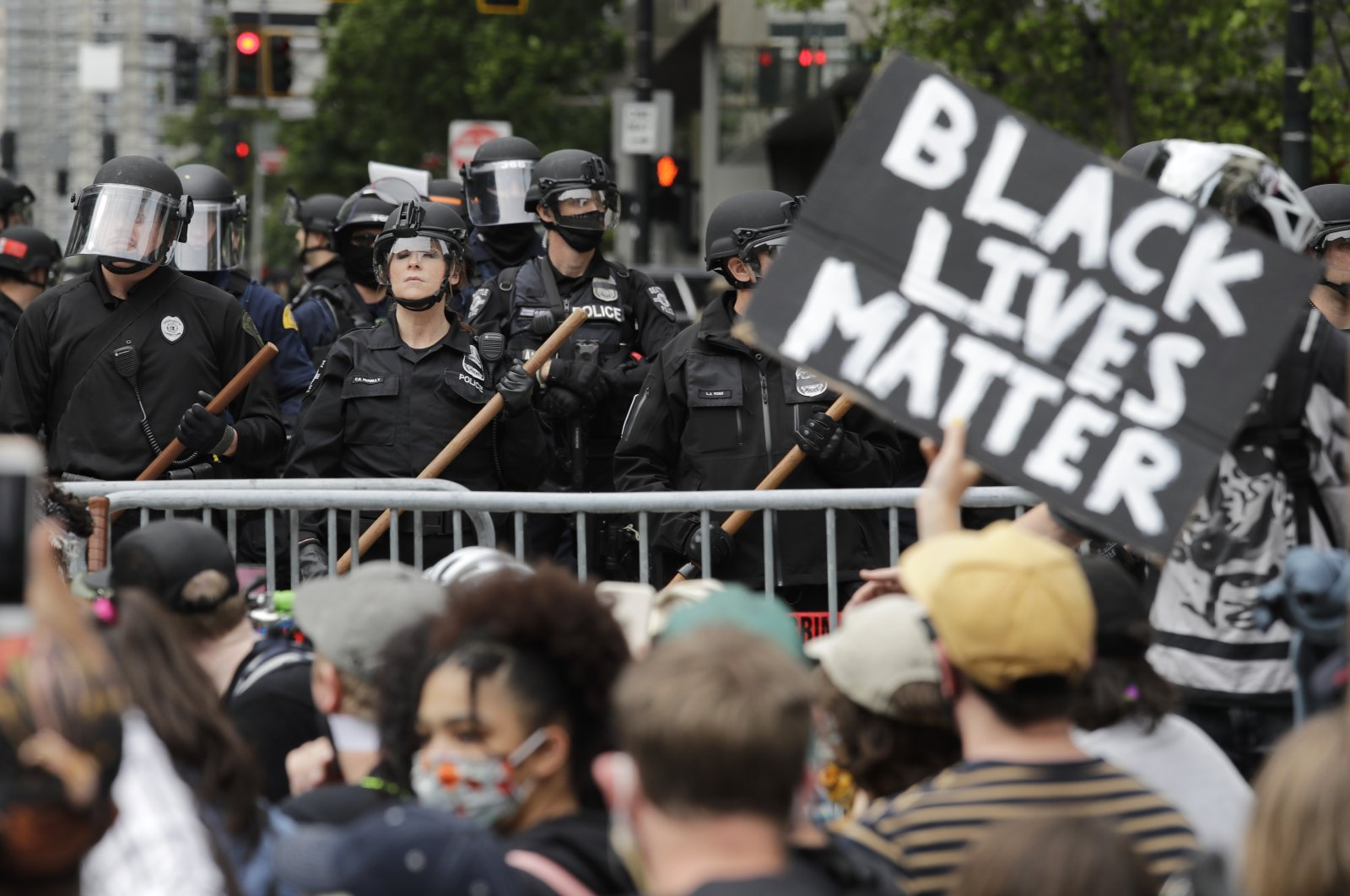 Police officers behind a barricade look on as protesters fill the street in front of Seattle City Hall, following protests over the death of George Floyd, a black man who was killed in police custody in Minneapolis, Seattle, Washington, U.S., June 3, 2020. (AP Photo)