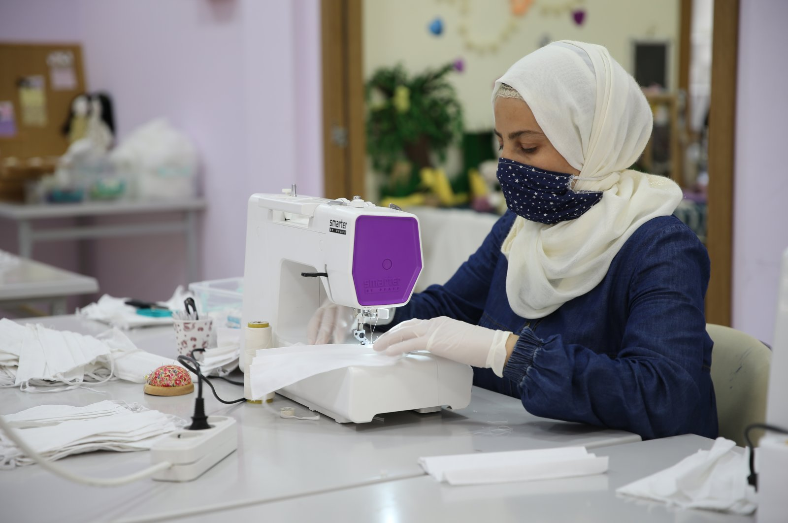 A Syrian woman sews a mask to be worn for protection against COVID-19 in Hatay, Turkey, June 14, 2020. (AA Photo)