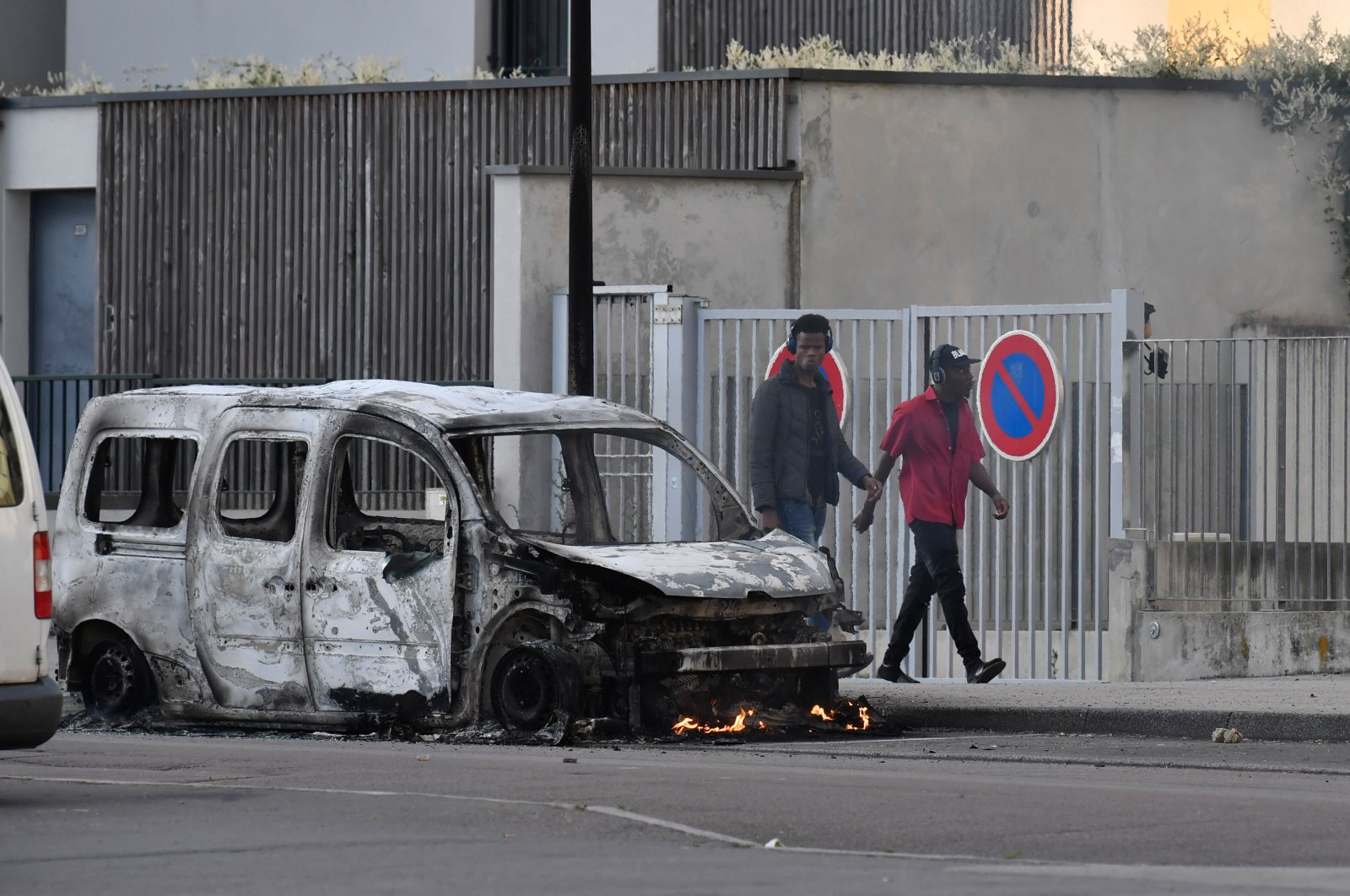 People walk past a burnt van in the Gresilles area of Dijon, France, June 15, 2020. (AFP Photo)
