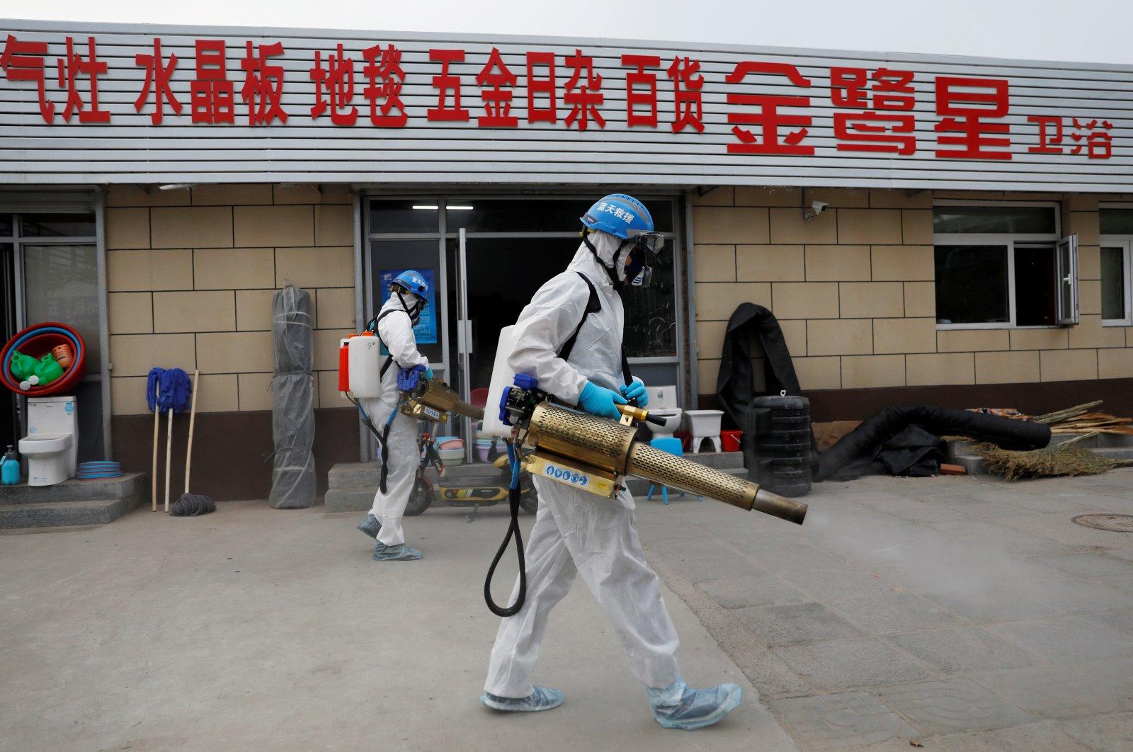 Volunteers in protective suits disinfect the Nangong comprehensive market, Beijing, China, June 18, 2020. (Reuters Photo)
