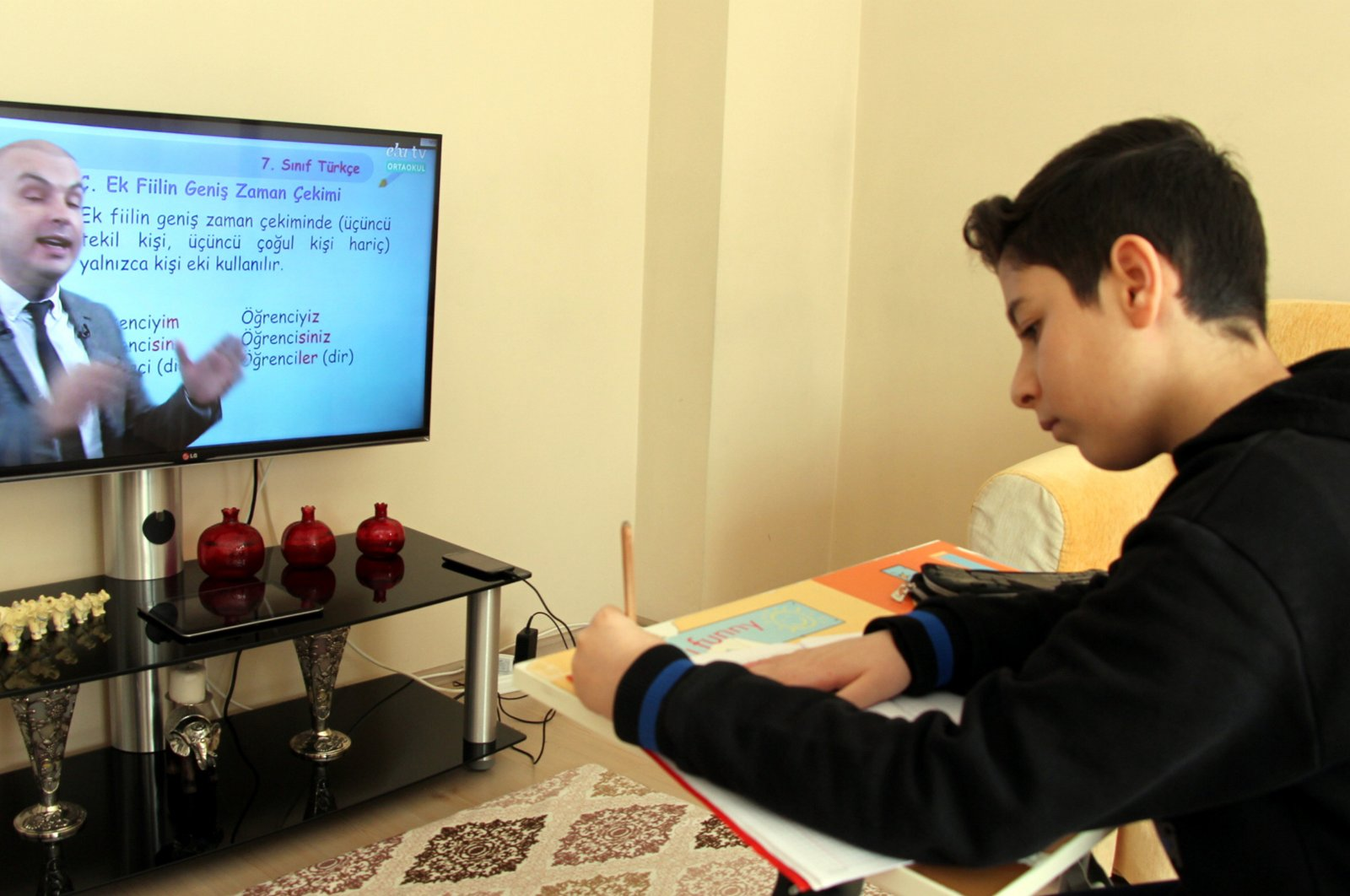 A student takes notes as he watches a remote education program, in Elazığ, Turkey, in this undated photo. (AA Photo)