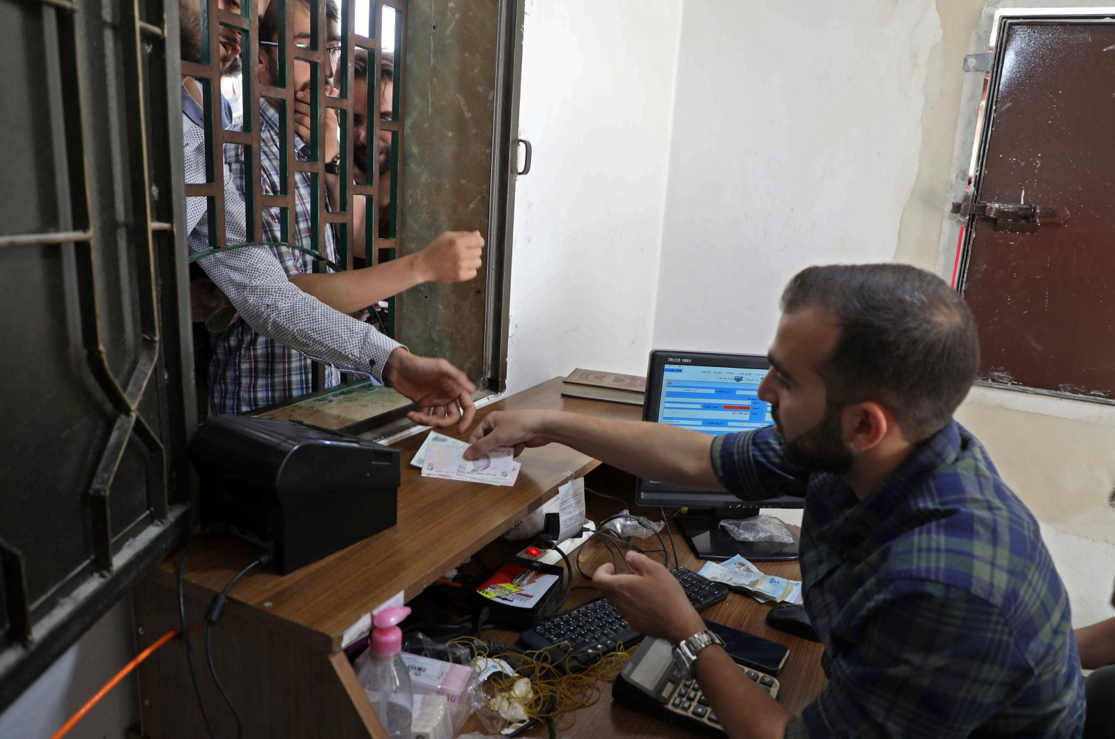 A Syrian man receives Turkish liras at a currency exchange shop in the town of Sarmada in Syria's northwestern Idlib province, June 15, 2020. (AFP Photo)