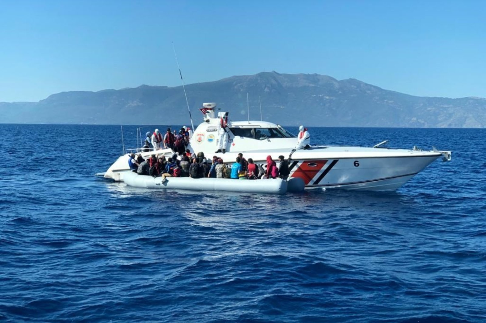 Migrants are being taken to a Turkish Coast Guard boat, Aegean Sea, June 19, 2020. (IHA Photo)