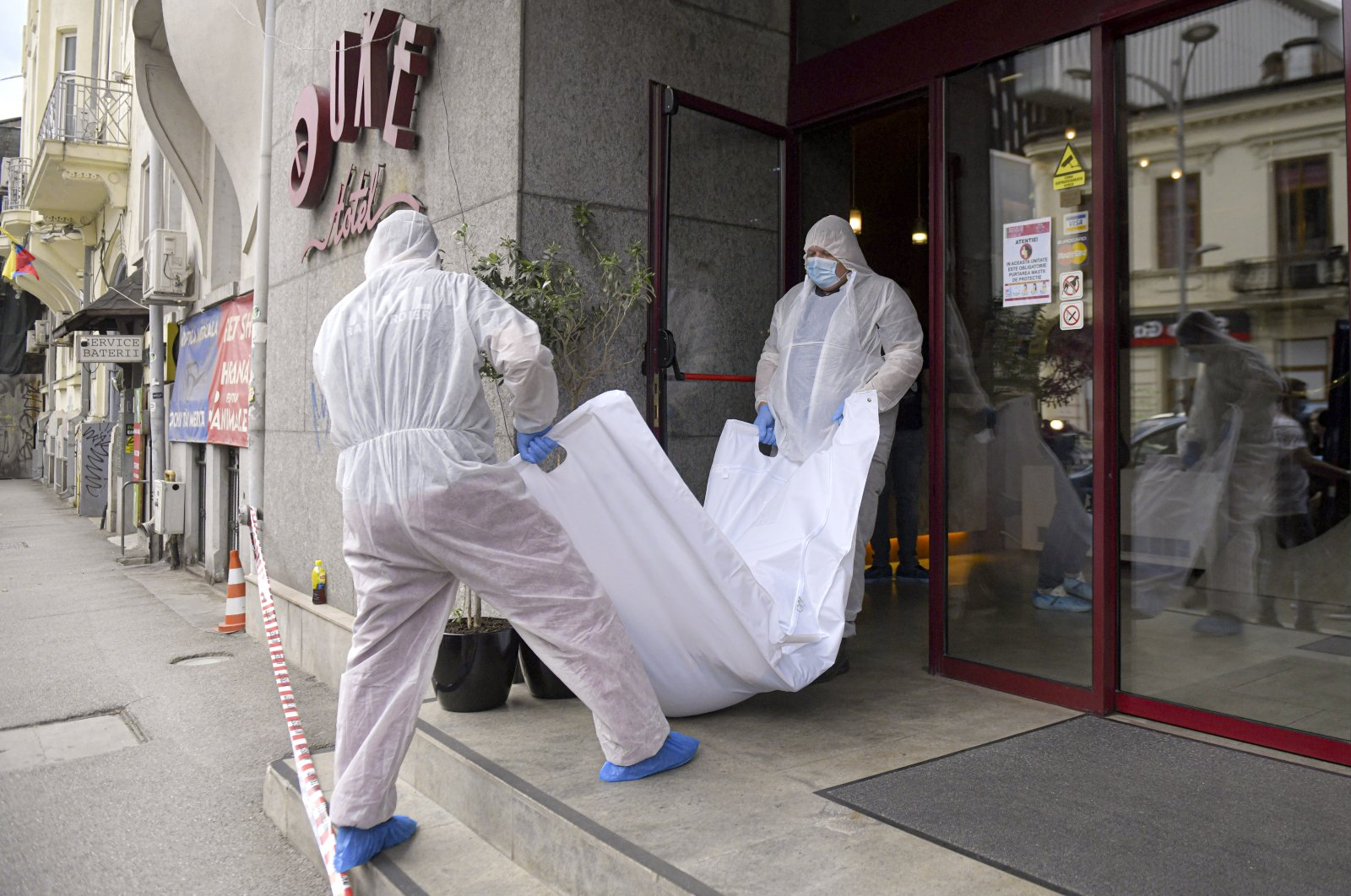Forensic workers carry a body from a hotel downtown Bucharest, Romania, June 19, 2020. (AP Photo)