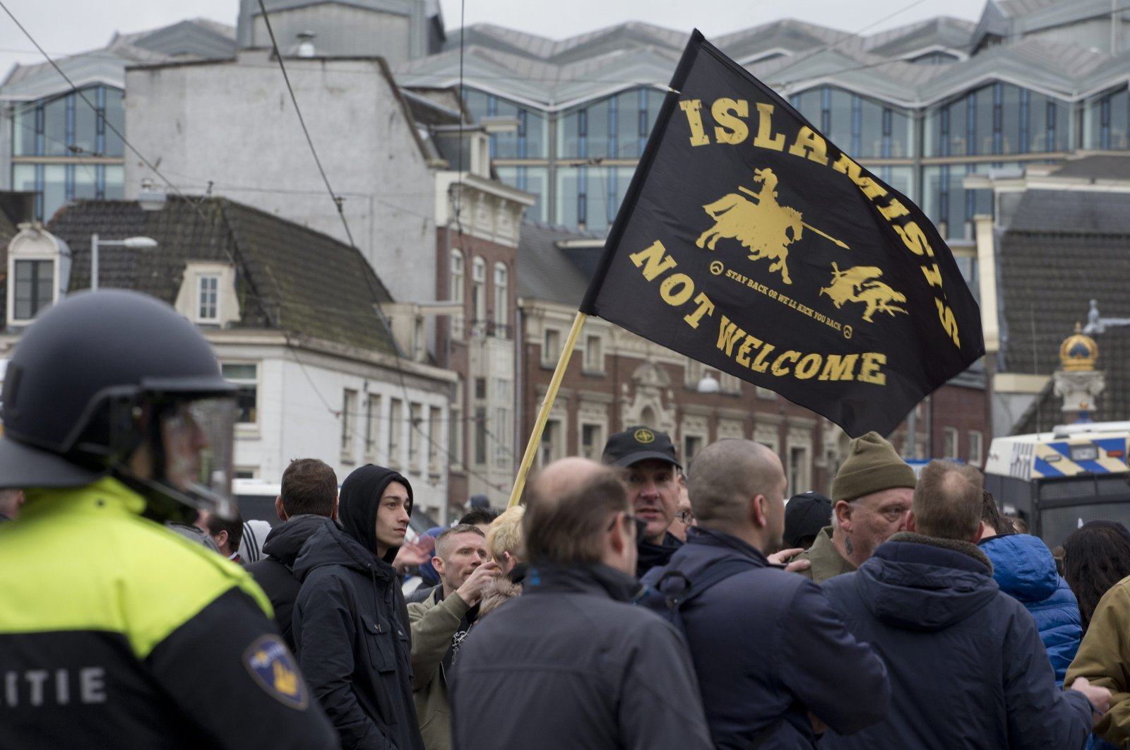 """Riot police separate pro- and anti- immigration demonstrators as a man waves a flag reading """"Islamists Not Welcome"""" during a far-right Pegida demonstration in Amsterdam, Netherlands, Feb. 6, 2016. (AP Photo)"""