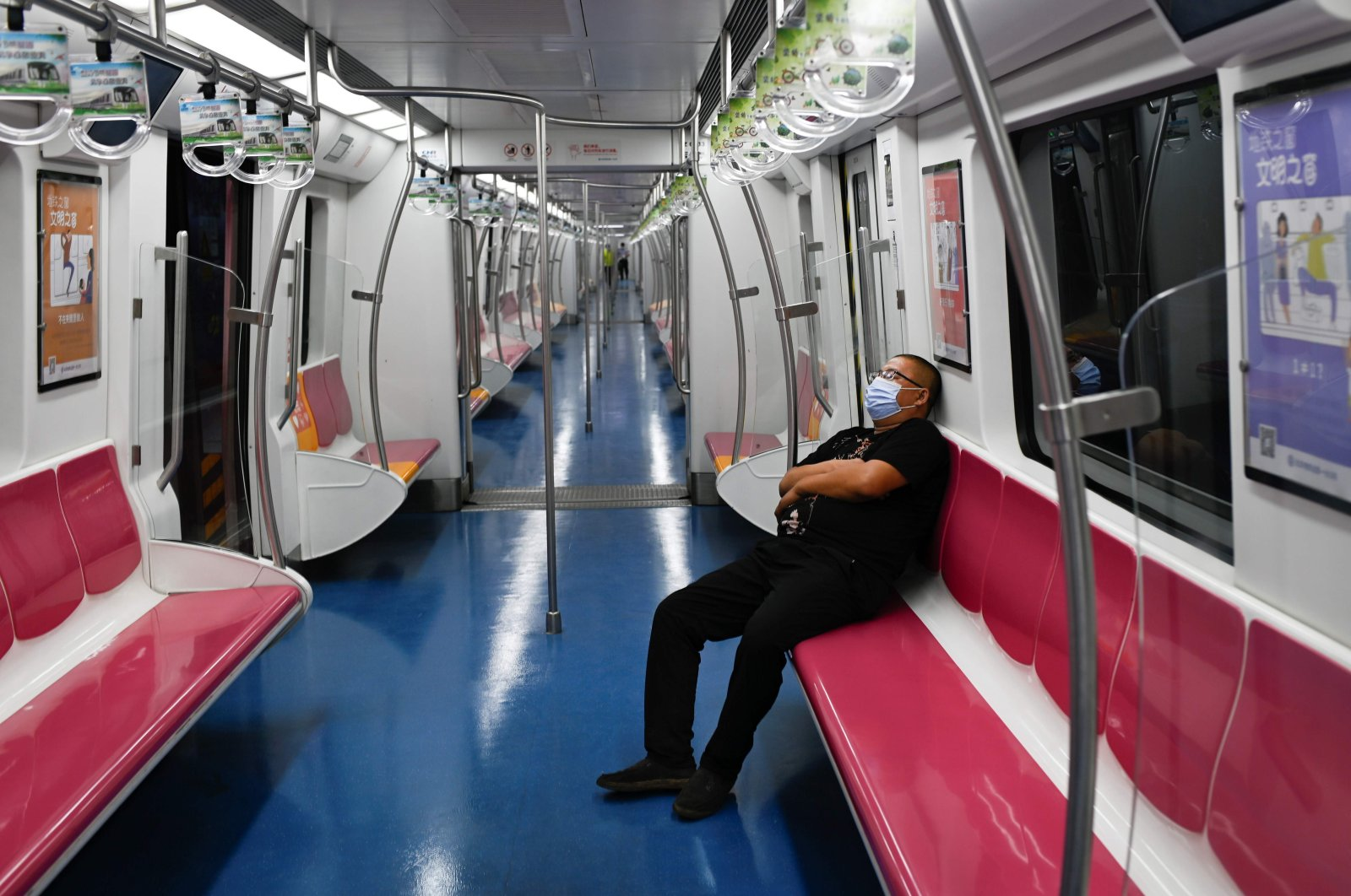 A man wearing a face mask sits on a subway train in Beijing on June 20, 2020 (AFP Photo)