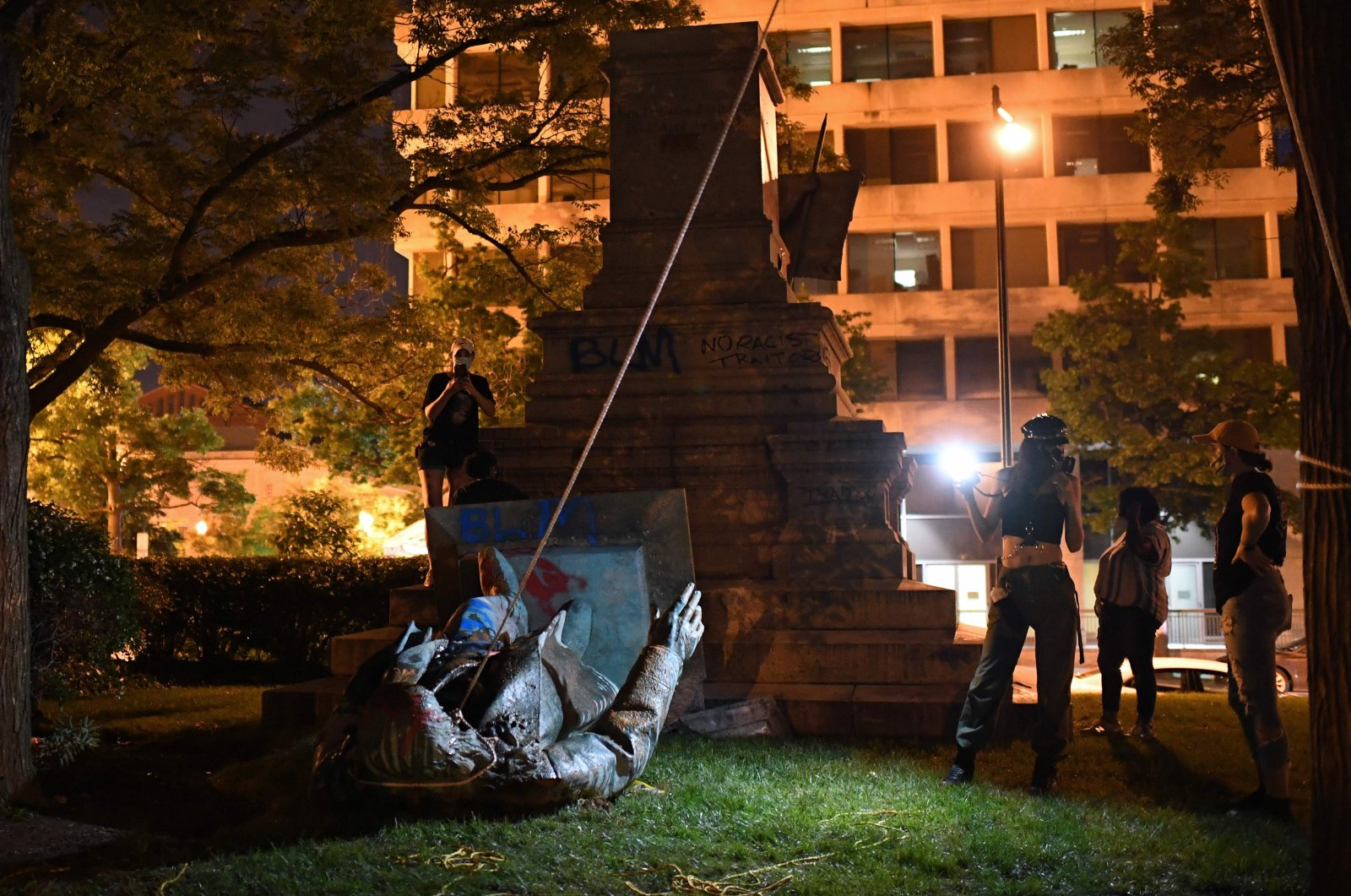 People stand around the statue of Confederate general Albert Pike after it was toppled by protesters at Judiciary Square in Washington, DC on late June 19, 2020. (AFP Photo)