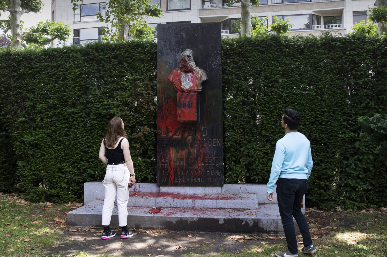 A couple stop to look at a bust of Belgium's King Leopold II, which has been damaged by red paint, graffiti and cement, at a park in Ghent, Belgium on Friday, June 19, 2020. Protests sweeping the world after George Floyd's death in the U.S. have added fuel to a movement to confront Europe's role in the slave trade and its colonial past.(AP Photo)