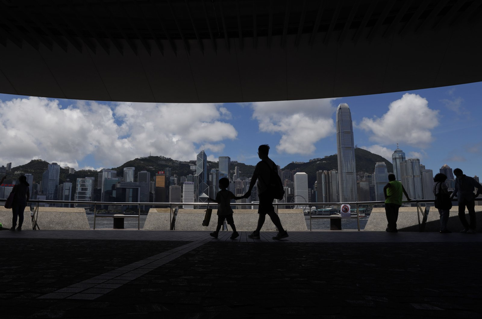 People walk at the waterfront of the Victoria Harbor of Hong Kong, June 20, 2020. China's top legislative body has taken up a draft national security law for Hong Kong that has been strongly criticized as undermining the semi-autonomous territory's legal and political institutions. (AP Photo)