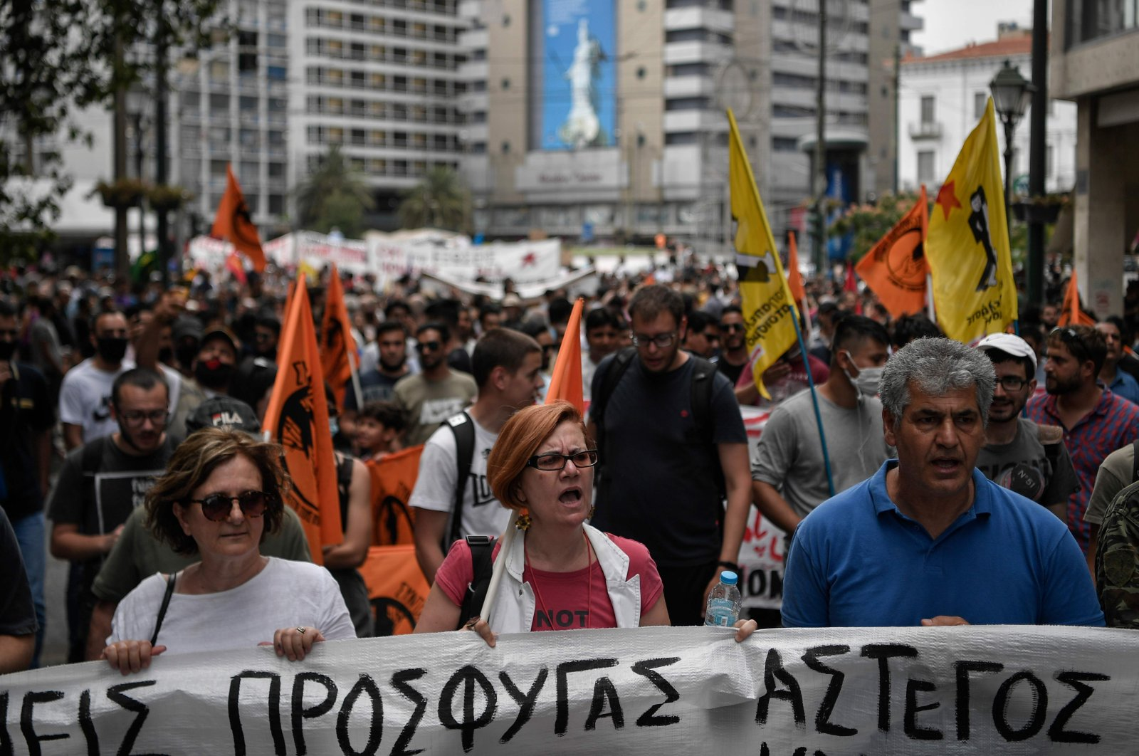 Solidarity groups and NGO's march behind banners as they participate in a rally marking World Refugee Day as they demand rights and housing for refugees and migrants in Athens, Greece, June 20, 2020, . (AFP Photo)