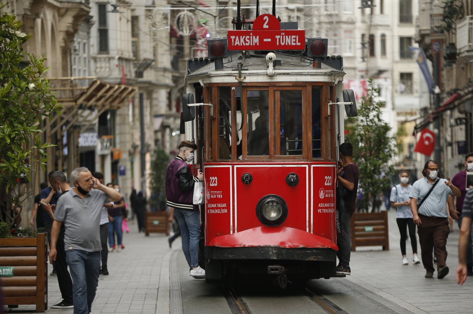 People, wearing protective masks against the spread of coronavirus, walk and use the tram on Istiklal street, the main shopping street in Istanbul, June 18, 2020. (AP Photo)